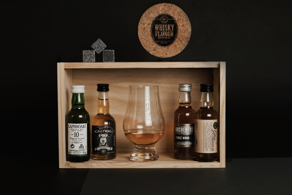 Whisky miniatures with a whisky glass, marble cubes and a coaster inside a wooden box