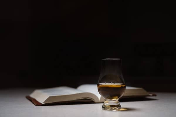 A book with a whisky tasting glass