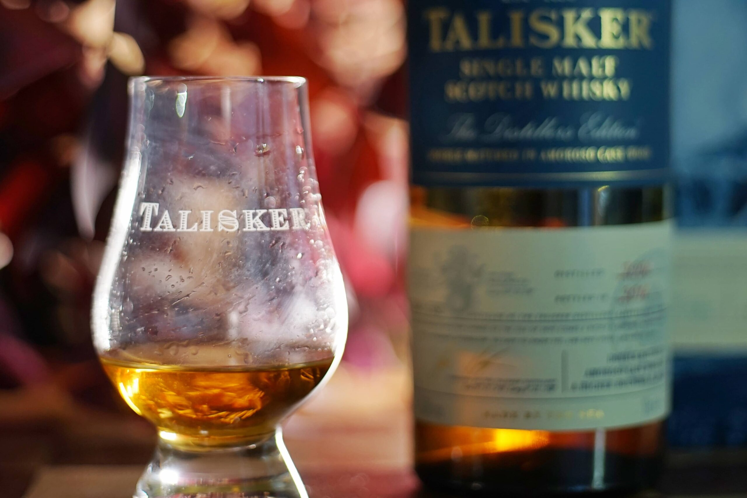 A talisker whisky bottle and a tasting glass with scotch on it