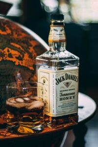 Bottle of Jack Daniels Honey near a globe