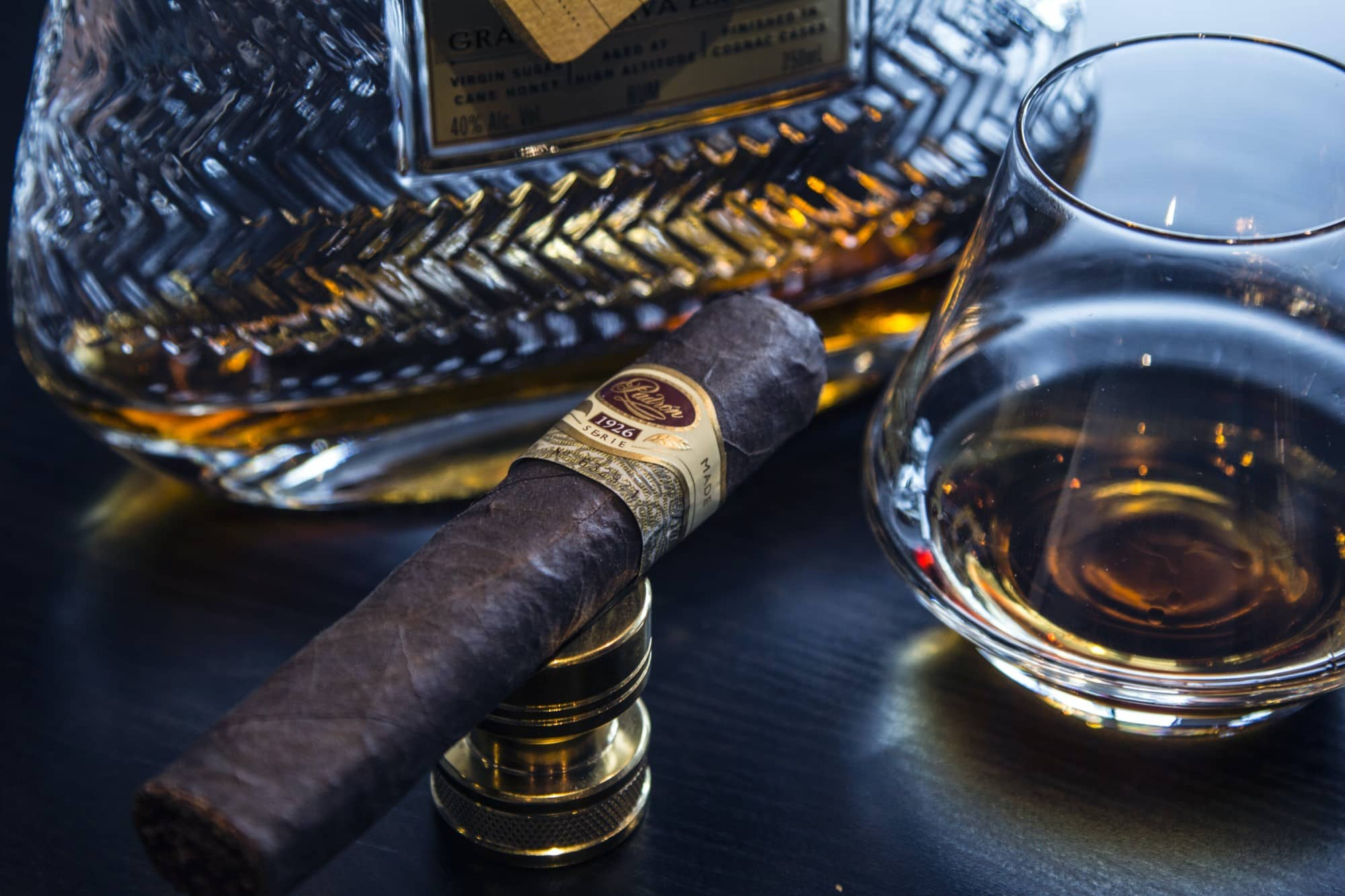 Cigar next to a glass and bottle of whisky