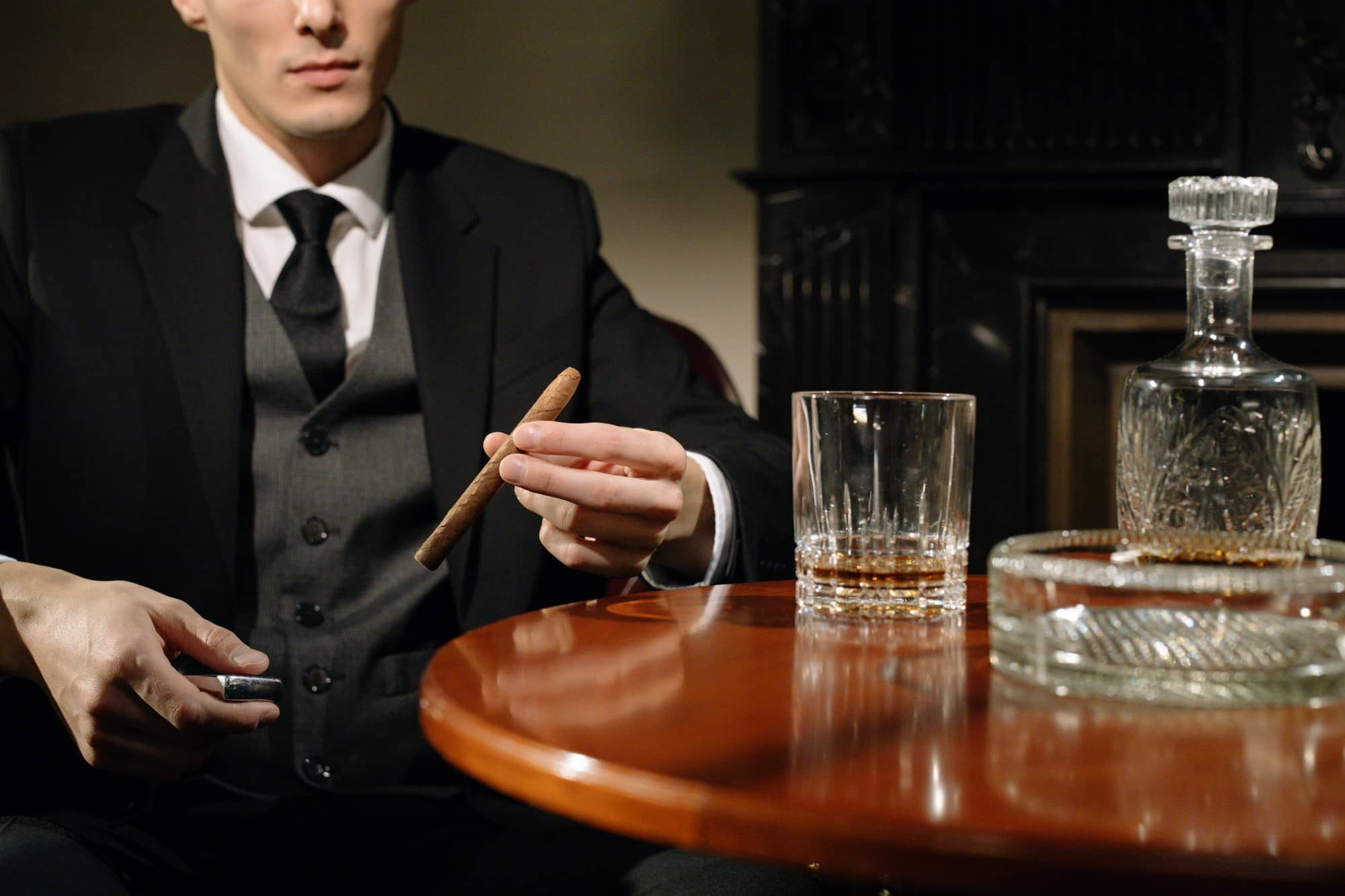 Gentleman seated at a table with a glass of whisky and a cigar