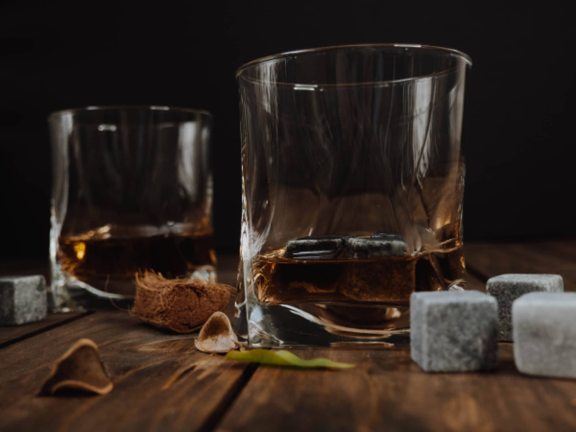 Two glasses of whisky close to a few whisky stones