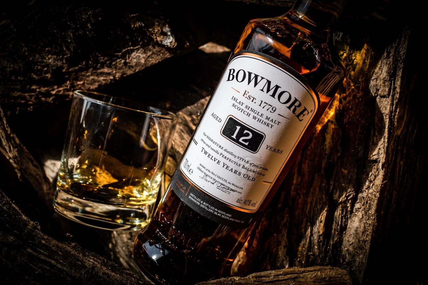 Glass of whisky and a bottle of Bowmore 12 laid down in wood