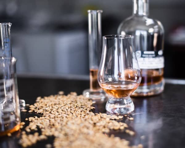 Table with a glass and scotch bottle with barley spreaded on top